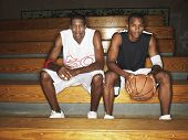 Portrait of two basketball players sitting on bench
