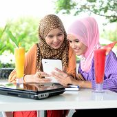 stock photo of muslimah  - Two young pretty Asian muslim business woman in head scarf with book laptop - JPG