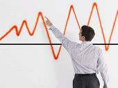 Rear view of a businessman pointing at graph