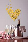 Champagne and glasses on round table on room  background