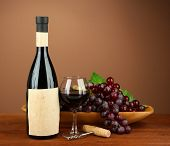 Composition of wine bottle, glass and  grape, on brown background