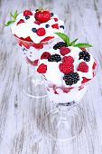Natural yogurt with fresh berries on wooden background