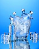 Minibar bottles in bucket with ice cubes,  on blue background