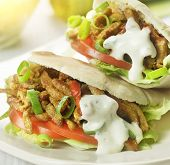 image of shawarma  - pita stuffed with shawarma tomato lettuce and a topping of garlic sauce served on a white plate - JPG