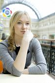 Young Attractive Blond Pensive Woman Sitting At Table In Cafe In State Department Store. Moscow