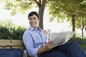 Happy young businessman with sandwich and newspaper looking away while sitting on bench outdoors