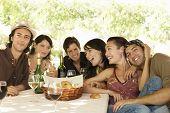 Retrato de jóvenes amigos con bebidas y cesta de pan en la mesa disfrutando de fiesta