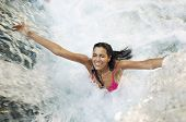 High angle view of young woman with arms outstretched enjoying waterfall