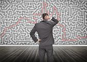 Puzzled businessman looking at a maze drew on a wall