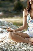 Recorta la imagen de mujer joven meditando en posición de loto, por el río del bosque