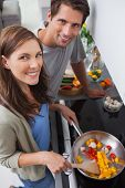 Couple cooking vegetables in the kitchen and smiling at camera