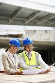 Architekten und Bau-Manager lesen Blaupause am Standort