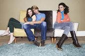 Young woman sitting with arms crossed by hugging couple on sofa