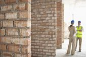 Blurred architect and construction manager at site with focus on brick walls