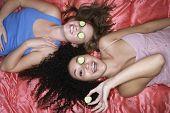 Draufsicht von zwei Mädchen im Teenageralter liegend Rosa Blatt mit Gurken über die Augen