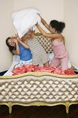 pic of pillow-fight  - View of three teenage girls pillow fighting on funky bed - JPG