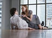 Young woman seducing businessman on office floor