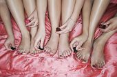 foto of slumber party  - Closeup of teenage girls painting toenails on pink bedsheet - JPG