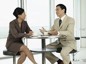 Businessman and woman sitting at table and talking to each other