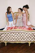 Teenage girls at slumber party kneeling on funky bed