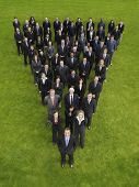 Elevated view of large group of business people standing in triangle formation