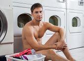 Retrato de homem nu semi com cesto de roupa suja esperando para lavar a roupa