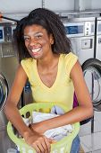 Portrait of happy young woman with basket of clothes sitting in laundromat