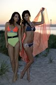 Two fashion models posing on the beach dunes wearing sexy swimsuits on sunset time