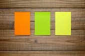 Three Colorful Post It Notes On Wooden Background