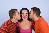 foto of threesome  - Two men trying to kiss a woman and she is surprised and making a funny face on blue background - JPG