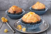 Muffins With Raisins In Blue Wrappers On Rustic Wood Background