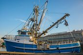 stock photo of fisherman  - Commercial fishing vessel with power block moored at fishermen - JPG