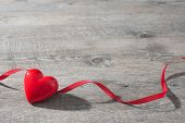 stock photo of february  - Heart with red ribbon on old wooden Valentines Day background - JPG