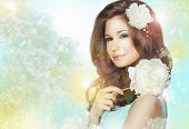Portrait Of Quiet Romantic Woman With Flowers Over Colored Bokeh Background