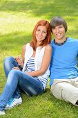 Teenage couple sitting on grass embracing in sunny park