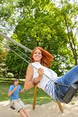 Two teenagers on swing playground in park smiling at camera