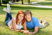 Smiling teenage couple lying in sunny park enjoy first love