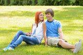 Teenage couple sitting on grass looking at each other summer
