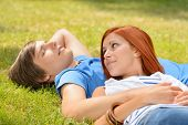 Teenage couple lying on grass summer girl looking at boyfriend