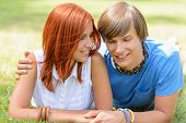 Teenage boyfriend and girlfriend holding hands lying on grass sunny