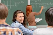 Smiling student girl sitting front of chalkboard during mathematics lesson