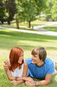 Teenage couple lying sunny park grass looking at each other