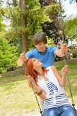 Teenage couple girl sitting on swing in park sunny day