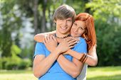 Young loving couple hugging in sunny park smiling pure romance
