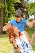 Boyfriend and girlfriend enjoying date sitting on swing in park