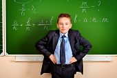 Smart schoolboy stands at the blackboard in the classroom. Education.