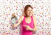 Happy Redhead Girl Holding A Clock Over Cute Background