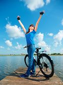 Young happy woman raised hands up in joy standing near her bicycle, outdoor shoot