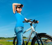 Young woman is standing in front of her bicycle, outdoor shoot