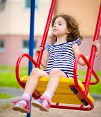 Young girl is swinging in playground, outdoor shoot